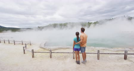 wai o tapu : New Zealand tourists. Couple on travel at Champagne pool at Wai-O-Tapu pools Sacred Waters. Tourist attraction in Waiotapu, Rotorua. Active geothermal area, Okataina Volcanic Centre Taupo, New Zealand Stock Footage