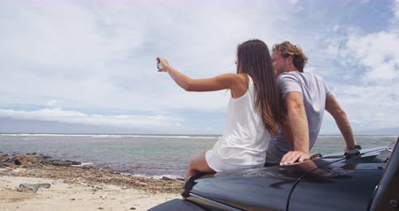 lanai : Couple taking selfie using smartphone at Shipwreck beach. Male and female hikers are sitting on offroad vehicle car trunk enjoying summer vacation on Lanai, Hawaii, USA.