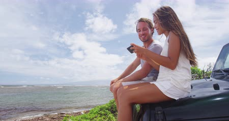 lanai : Happy multiethnic couple using smartphone at Shipwreck beach, Hawaii. Male and female hikers are sitting on offroad car trunk relaxing during summer vacation on Lanai, Hawaii looking at phone pictures