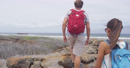 lanai : Hiking couple walking on rocks at Shipwreck beach. Woman and man hikers are carrying backpacks. People on Hawaiian vacation on Lanai, Hawaii. Stock Footage