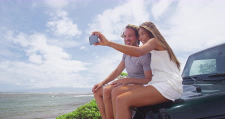 lanai : Happy couple taking selfie using smartphone at Shipwreck beach, Lanai. Young tourists are sitting on offroad vehicle trunk enjoying summer vacation on Lanai, Hawaii, taking phone pictures.