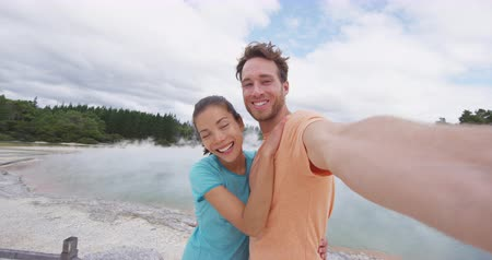 wai o tapu : Tourists couple taking selfie at New Zealand Waiotapu pools travel destination. Young people having fun sightseeing at colorful geothermal hot springs ponds, Waiotapu, Rotorua, New Zealand.