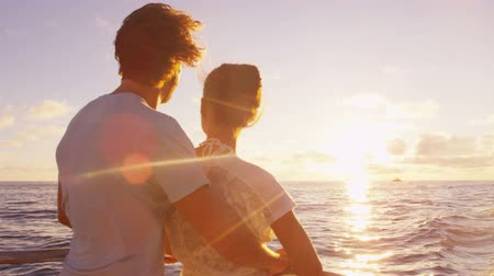 крейсерский : Cruise ship vacation couple enjoying sunset view sailing on small cruise boat at sea. Romantic couple on honeymoon travel at sea looking at sunset. Стоковые видеозаписи
