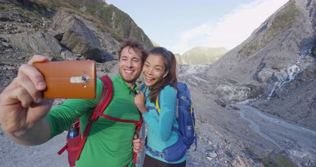 glacier national park : Selfie couple taking phone self-portrait on New Zealand by Franz Josef Glacier. New Zealand tourists smiling happy in nature by Franz Josef Glacier, Westland Tai Poutini National Park. Stock Footage