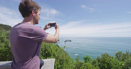 lookout point : Tourist man taking photos with smart phone at Knights Point Lookout West Cost region of South Island, New Zealand. Tourist enjoying view of nature landscape of coastline, New Zealand.