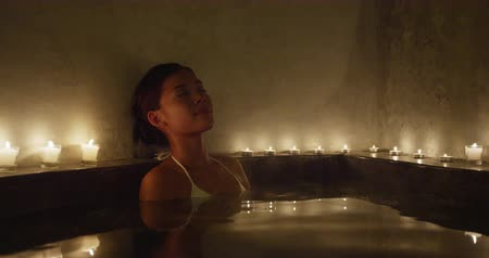 джакузи : Jacuzzi spa woman relaxing in hot tub whirlpool enjoying bath with candlelight. Beautiful young Asian woman enjoying pampering luxury lifestyle.