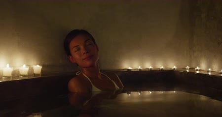 джакузи : Relaxation and luxury at spa jacuzzi hot tub resort. Woman taking a bath at night by candlelights outside Стоковые видеозаписи