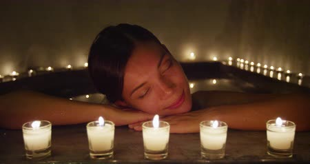 джакузи : Beautiful woman resting head on the edge of Jacuzzi. Relaxed female is leaning by lit candles at beauty spa. She is resting during her vacations.