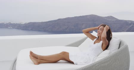 Санторини : Woman relaxing in sunbed at luxury apartment terrace outdoors on with incredible view of Caldera on Santorini, Greece, Europa. Стоковые видеозаписи