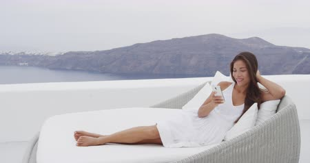 УВР : Phone - woman relaxing on outdoor sofa using smartphone social media app. Home living outside patio furniture. Young adult texting on mobile cell phone lying on sofa with Oia Santorini background.