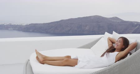 sen : Girl relaxing in sunbed at luxury apartment terrace outdoors on with incredible view of Caldera on Santorini, Greece, Europa.