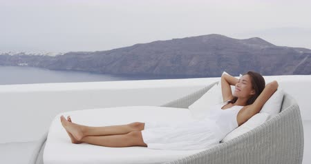 Санторини : Relaxed young woman reclining on lounge chair at resort terrace. Female is enjoying her vacations at Santorini. Scenic view of mountains and sea is in background. RED EPIC SLOW MOTION.