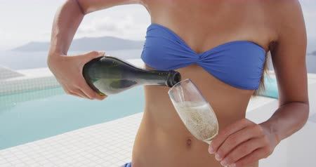 джакузи : Sexy bikini woman pouring a glass of champagne by jacuzzi pool on luxury outdoor summer terrace in resort hotel or home patio. Person holding an alcohol bottle on balcony with view travel destination.