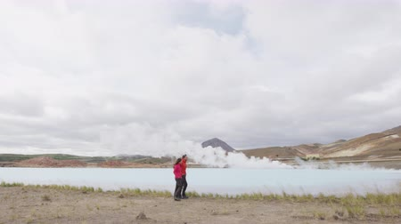 geotermální : Iceland travel people by geothermal energy power plant and hot spring in Namafjall in Lake Myvatn area. Couple on travel in Icelandic nature landscape.