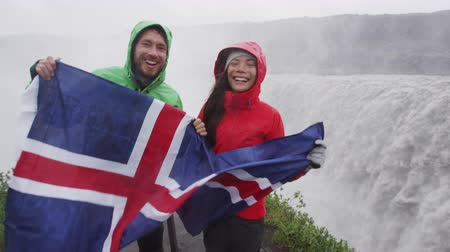 алмаз : Travel tourists fun by Dettifoss waterfall on Iceland showing Icelandic flag. People visiting famous tourist attractions and landmarks on Diamond Circle. Happy tourist couple enjoying vacation travel.