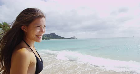 Оаху : Happy young woman standing at Waikiki Beach. Sensuous female with windswept hair is looking at sea view in Honolulu. She is wearing black bikini top during summer vacation at island.
