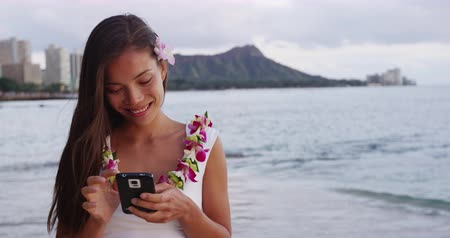 naszyjnik : Happy young woman using smartphone at Waikiki Beach. Smiling female tourist is wearing orchid lei garland during vacation at island in Honolulu. She is text messaging using mobile phone on shore.