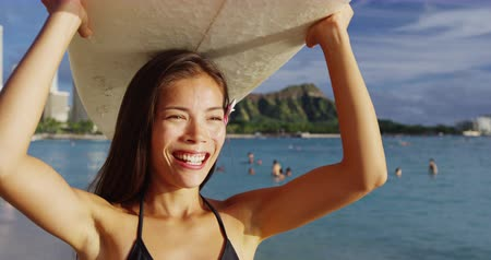 Оаху : Happy young woman carrying surfboard on head at Waikiki Beach. Beautiful female tourist is walking on shore during summer vacation at island in Honolulu. She is enjoying by sea against sky. Стоковые видеозаписи
