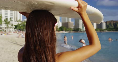 Оаху : Young woman carrying surfboard on head at Waikiki Beach. Female tourist with long brunette hair is walking on shore during summer vacation. She is enjoying at island in Honolulu.