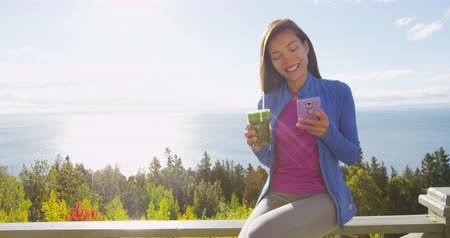 шпинат : Healthy eating girl drinking green smoothie detox using cell phone in autumn fall foliage nature retreat. Happy woman using smartphone app on weight loss diet vegan nutrition cleanse.
