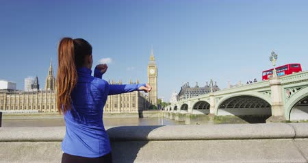 westminster : London lifestyle woman running and stretching near Westminster Bridge and Big Ben London. Female runner jogging training in city. Fitness girl smiling happy on Westminster Bridge, London, England. Stock Footage