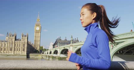 Бен : London running woman training for marathon. Sport girl jogging in city near Big Ben and Westminster bridge, exercising on the way to work. Morning workout to the office. SLOW MOTION.