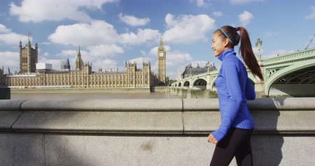 język angielski : Woman running in London in front of Big Ben. Female runner on Westminster Bridge. Multicultural Asian Caucasian girl jogging training in London City, England, United Kingdom.