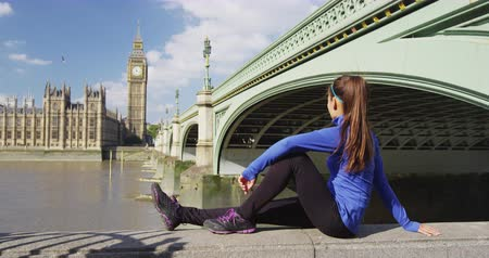 Бен : London city fit girl runner taking running break at Big Ben Westminster bridge, famous tourist destination in Europe. Athlete jogging woman on rest outdoor in autumn.