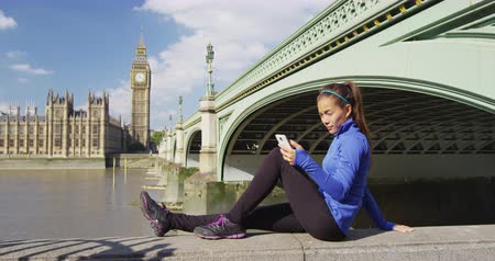 westminster : London phone runner sport fit woman using mobile smartphone at Big ben on jogging break resting during autumn workout. Active fitness Asian girl enjoying view of Westminster, Britain, UK
