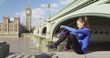 great britain : Running woman runner tying shoes going jogging in London by River Thames and Westminster Bridge. SLOW MOTION.