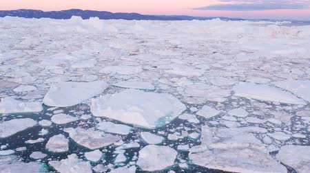 climate : Icebergs in Icefjord aerial drone video of amazing nature landscape on Greenland. Iceberg and ice in fjord from melting glacier. Ilulissat icefjord, Disko bay, Greenland. Affected by climate change. Stock Footage