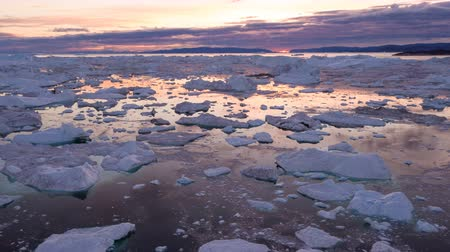 disko bay : Arctic nature landscape with icebergs in Greenland icefjord with midnight sun sunset  sunrise in the horizon. Aerial drone footage video of ice. Ilulissat Icefjord with icebergs from glacier.