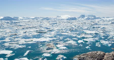 disko bay : Travel adventure in Arctic landscape nature with icebergs - tourist person looking at view of Greenland icefjord - aerial video. Man by ice and iceberg, Ilulissat Icefjord with glacier icebergs Stock Footage