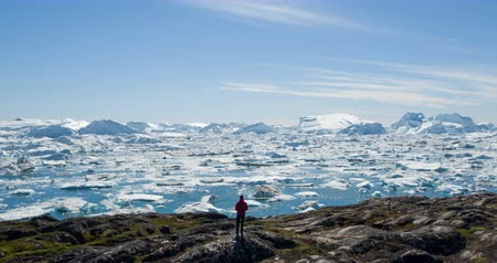disko bay : Travel wanderlust adventure in Arctic landscape nature with icebergs - tourist person looking at view of Greenland icefjord - aerial video. Man by ice and iceberg, Ilulissat Icefjord.