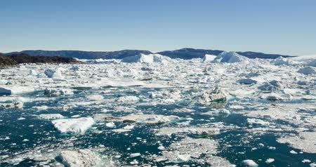 ilulissat : Ice and Icebergs in Icefjord - aerial video of arctic iceberg nature landscape on Greenland. Iceberg and ice in fjord from melting glacier. Ilulissat icefjord, Disko bay, Greenland. Climate change. Stock Footage