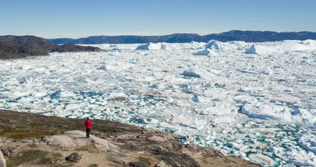ilulissat : Travel in arctic landscape nature with icebergs - Greenland tourist man explorer - tourist person looking at amazing view of Greenland icefjord - aerial video. Man by ice and iceberg in Ilulissat.