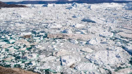 disko bay : Arctic landscape nature with icebergs and ice in Greenland icefjord. Aerial drone footage video of ice and iceberg. Ilulissat Icefjord with icebergs from Jakobshavn Glacier aka Sermeq Kujalleq glacier