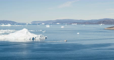 disko bay : Icebergs and tourist boat in Greenland iceberg landscape of Ilulissat icefjord with giant icebergs. Icebergs from melting glacier. Aerial drone video footage of arctic nature.