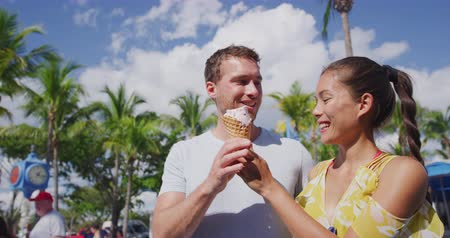 waffle : People eating ice cream - couple having fun laughing on travel vacation. Couple fort myers beach. Happy multiracial young couple shot on RED in SLOW MOTION.