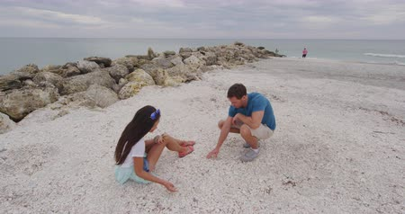 seashell : Shelling - People looking for Seashells on beach. Couple shelling picking up sea shells Sanibel Island, Florida. Sanibel Island near Fort Myers is know for shelling and sea shell collecting. Stock Footage