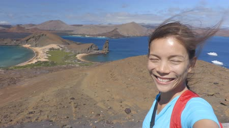 pináculo : Adventure travel - Galapagos tourist selfie video on Bartolome Island. Vacation woman taking selfie self portrait video at famous viewpoint and visitor site of iconic landscape with Pinnacle Rock.