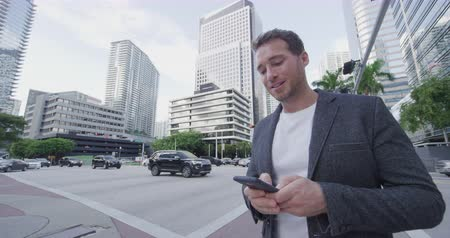 cbd : Young businessman portrait using phone walking in Miami. Smiling confident business man walking using cell smartphone front of modern condo building. City lifestyle people in Miami, Florida, USA.