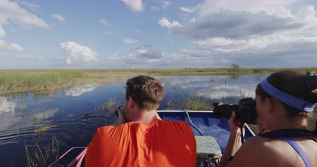 fotky : Everglades Airboat tour and alligator - tourists taking picture of alligators on ecotourism travel vacation in Everglades Florida. Airboat tours are a famous tourist activity in the Everglades.