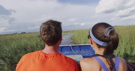 jacaré : Everglades Airboat tour in Everglades in Florida - tourists couple on private air boat tour. Airboat tours are a famous tourist attraction in the Everglades. RED cinema camera in SLOW MOTION.