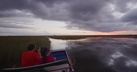 orta hava : Airboat in Everglades in Florida. tourists on tour at sunset. Airboat tours are a famous tourist attraction in the Everglades. RED cinema camera in SLOW MOTION.