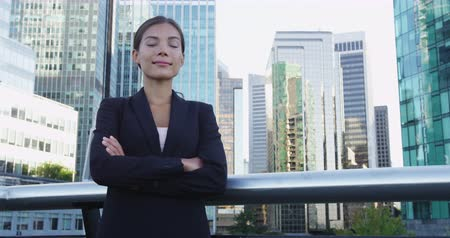 gururlu : Women in Business concept. Confident young businesswoman standing arms crossed against office buildings. Beautiful female executive is standing in city business center.