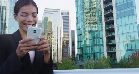 перила : Smiling young businesswoman using smartphone against office buildings. Beautiful business professional is holding mobile phone by railing in financial district. She is wearing suit in city. Стоковые видеозаписи