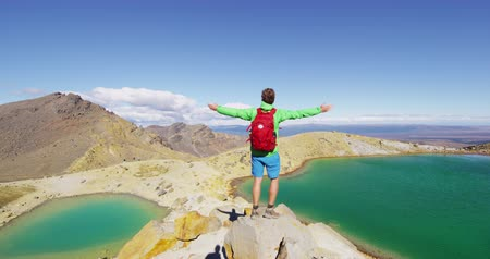 braços levantados : Adventure Travel Wanderlust - Man Standing Arms Outstretched On New Zealand hike tramping by Emerald Lakes. Healthy backpacker hiking on Tongariro Alpine Crossing enjoying nature in New Zealand.