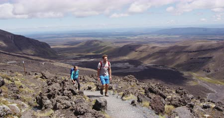 nový zéland : Young man and woman hiking wearing backpacks walking in amazing volcanic landscape in New Zealand. Couple backpackers hiking in Tongariro National Park. Stunning landscape, Tongariro Alpine Crossing.