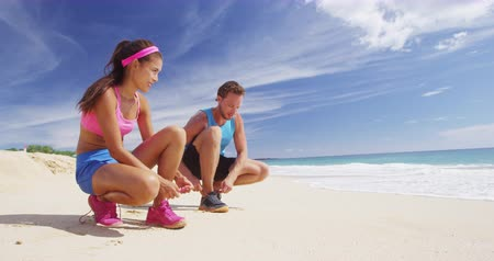 koronka : Low-angle view of young woman and man in blue and pink sportswear sitting on beach and tying their sport shoes over cloudy sky and sea waves background. Copyspace